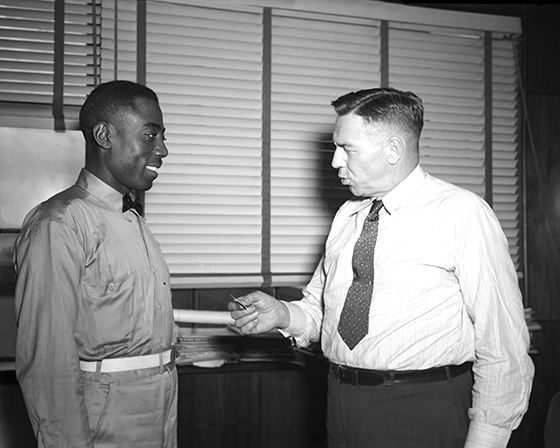 Hill receiving 10-year service pin from Woolman, 1945