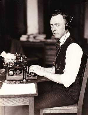 Paul F Godley with typewriter & headphones
